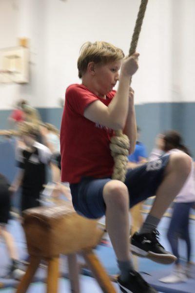 Junge schwingt an einem Seil im Parcours