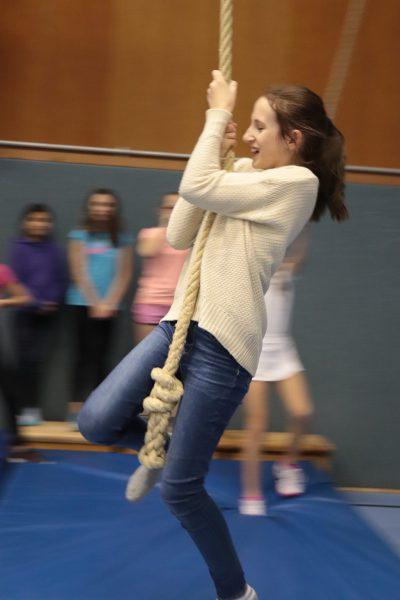 Mädchen schwingt an einem Seil im Parcours